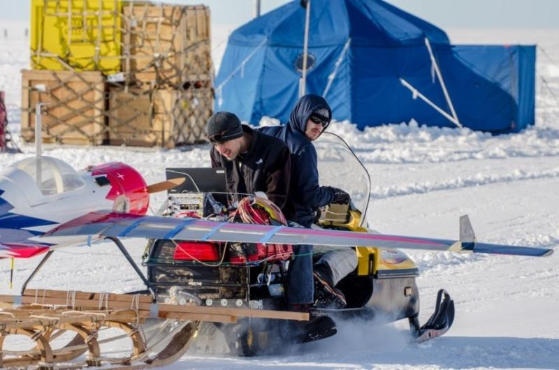Photo of ground test of dual-frequency radar installed inside G1X UAS with antennas integrated in wings. The UAS was attached to a sled and towed behind a snowmobile to measure the runway's ice thickness. In this photo, Carl Leuschen is conducting the radar test and Nicholas Brown is driving the snowmobile. (Photo courtesy of Alec Bowman).